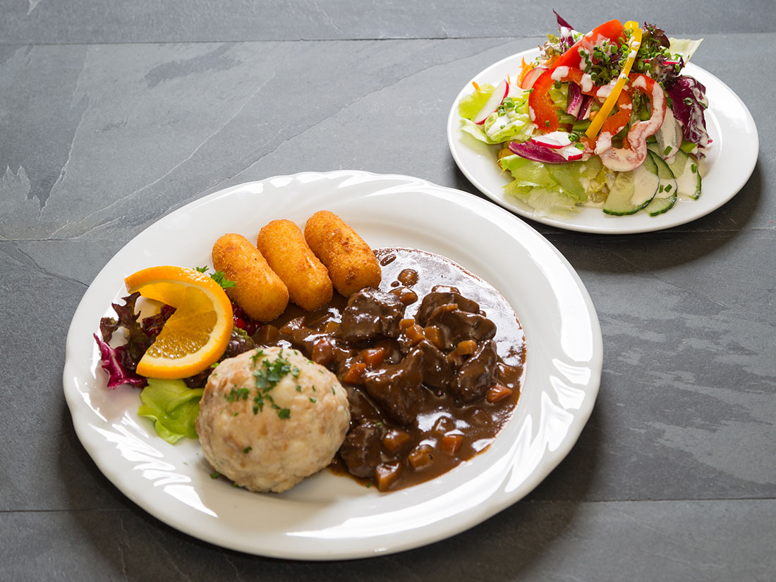 Goulash from venison with croquettes, dumplings and salad